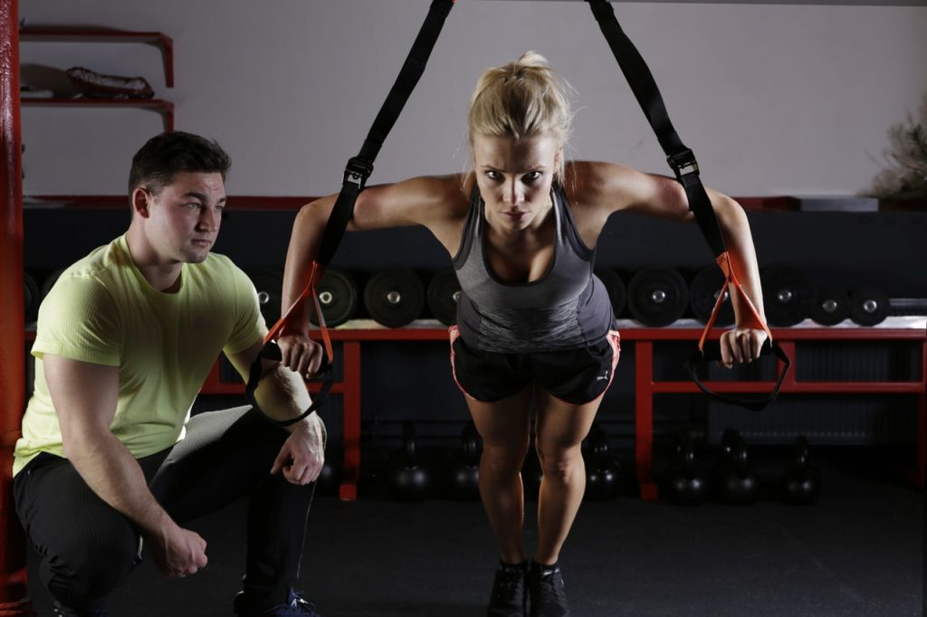 Women working out in a gym with a personal trainer